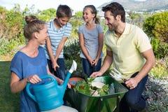 Lycklig ung familj som tillsammans arbeta i trädgården Royaltyfri Bild