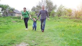 Lycklig ung familj som tillsammans spenderar tid utanför i grön natur
