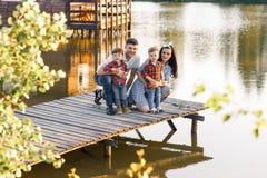 Lycklig ung familj som tillsammans spenderar tid utanför i grön natur Föräldrar som spelar med, kopplar samman utanför Royaltyfri Bild