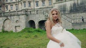 Lycklig ung flicka i en bröllopsklänningbanhoppning och stock video
