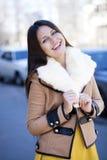 Lycklig ung flicka i fårskinnlag på en bakgrund av staden arkivfoto