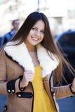 Lycklig ung flicka i fårskinnlag på en bakgrund av staden royaltyfri foto