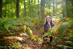 Lycklig ung flicka i skog på en nedgångdag Arkivfoto
