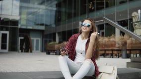 Lycklig ung flicka i solglasögon som tycker om musik på hennes smartphone på momenten nära kontorsmitt lager videofilmer