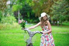 Lycklig ung flicka med cykeln och blommor Royaltyfri Foto