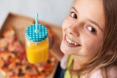 Lycklig ung flicka med en ask av pizza och en tillbringare av ju för ny frukt royaltyfri bild