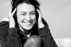 Lycklig ung flicka med hörlurar som lyssnar till musik på taket och le Royaltyfria Bilder