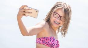 Lycklig ung flicka med tand- hänglsen som gör selfhie på stranden i varm dag för sommar royaltyfria foton