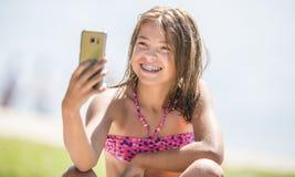 Lycklig ung flicka med tand- h?nglsen som g?r selfhie p? stranden i varm dag f?r sommar arkivbilder