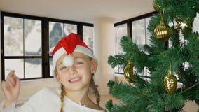 Lycklig ung flicka som dansar nära julträd i röd hatt för jultomten Lycklig ung caucasian flicka jul min version för portföljtree lager videofilmer