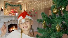Lycklig ung flicka som dansar nära julträd i röd hatt för jultomten Den lyckliga unga caucasian flickan stänger sig inomhus upp d arkivfilmer