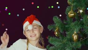 Lycklig ung flicka som dansar nära julträd i röd hatt för jultomten Lyckligt ungt caucasian flickaslut upp dekorerad jul lager videofilmer