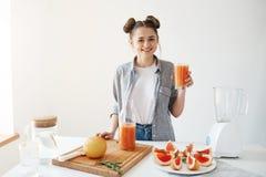 Lycklig ung flicka som ler se hållande exponeringsglas för kamera med den sunda detoxgrapefruktsmoothien över den vita väggen Royaltyfri Fotografi