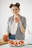 Lycklig ung flicka som ler se hållande exponeringsglas för kamera med den sunda detoxgrapefruktsmoothien över den vita väggen Royaltyfri Bild
