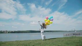 Lycklig ung flicka som poserar med färgglade bollar på sommarfjärden stock video