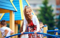 Lycklig ung flicka som spelar på utomhus- lekplats arkivbild