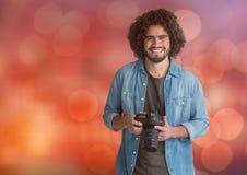 lycklig ung fotograf med kameran på händer Röd bokehbakgrund arkivbild