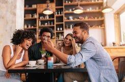 Lycklig ung grupp av vänner som använder mobiltelefonen på kafét royaltyfri fotografi