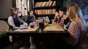 Lycklig ung grupp av vänner som möter i ett kafé lager videofilmer
