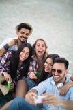 Lycklig ung grupp människor som tar selfies på stranden royaltyfria foton
