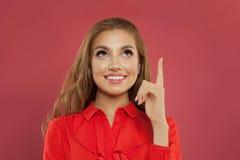 Lycklig ung härlig gladlynt kvinna som pekar upp på den färgrika rosa bakgrundsståenden Studentflicka som pekar fingret och ser u royaltyfria foton