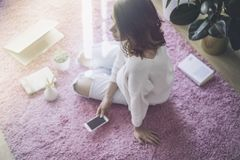 Lycklig ung härlig kvinna som använder elektroniska grejer, medan sitta på golvet i vardagsrummet Arkivfoton