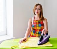 Lycklig ung härlig kvinnastrykningkläder. Royaltyfri Foto