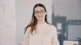 Lycklig ung härlig millennial affärskvinna som talar på modernt ljust kontorsutrymme, företags utbildningsseminarium arkivfilmer