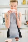 Lycklig ung hemmafru som dricker te med muffin Royaltyfria Foton