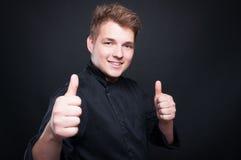 Lycklig ung kock som ler upp och ger tummar Royaltyfria Bilder
