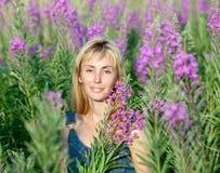 Lycklig ung kvinna i blommor som blommar sally Arkivbild