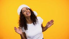 Lycklig ung kvinna i den Santa Claus hatten som har gyckel som ler på kameran, hälsning fotografering för bildbyråer