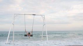 Lycklig ung kvinna i den vita baddräktridningen på gunga som tycker om havssikt h?rligt barn f?r kvinna f?r begreppsp?lsemester lager videofilmer