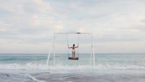 Lycklig ung kvinna i den vita baddräktridningen på gunga som tycker om havssikt h?rligt barn f?r kvinna f?r begreppsp?lsemester stock video