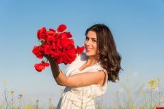 Lycklig ung kvinna i fältet med en vallmobukett Fotografering för Bildbyråer
