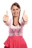 Lycklig ung kvinna i ge sig för dirndl tummar upp arkivbild