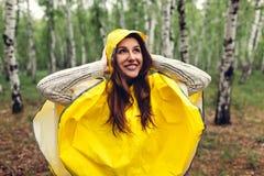 Lycklig ung kvinna i gul regnrock som går i vårskog under regn och har gyckel fotografering för bildbyråer