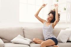 Lycklig ung kvinna i hörlurar på den beigea soffan royaltyfria foton