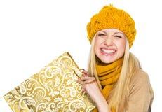 Lycklig ung kvinna i hatt och halsduk med shoppingpåsen Fotografering för Bildbyråer