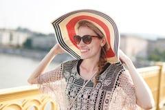 Lycklig ung kvinna i hatt som går på bron, friskhet Royaltyfri Fotografi