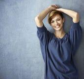 Lycklig ung kvinna i jeans som poserar på väggen fotografering för bildbyråer