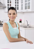 Lycklig ung kvinna i kök royaltyfri bild
