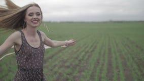 Lycklig ung kvinna i mörk klänning med det blom- trycket