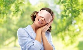 Lycklig ung kvinna i pajama och ?ga som sover maskeringen royaltyfria bilder