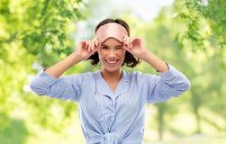 Lycklig ung kvinna i pajama och ?ga som sover maskeringen arkivfoto