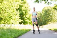 Lycklig ung kvinna i rollerblades som utomhus rider Fotografering för Bildbyråer