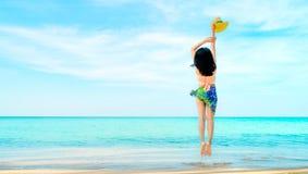 Lycklig ung kvinna i rosa hatt för swimwearhandinnehav och hoppa på sandstranden Koppla av och tycka om ferie på det tropiska par royaltyfria bilder