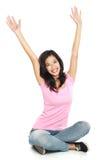 Lycklig ung kvinna i sammanträde för tillfälliga kläder med lyftt armsmilin Arkivfoto