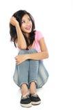 Lycklig ung kvinna, i sammanträde och att tänka för tillfälliga kläder Royaltyfri Bild
