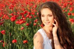 Lycklig ung kvinna i vallmofält Royaltyfria Bilder
